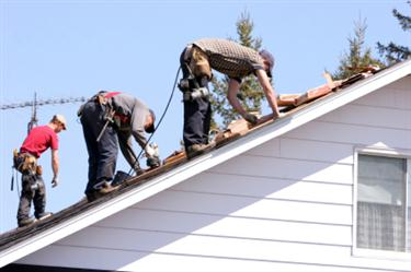 Roof Installation in Hyattsville MD. Three roofers laying new shingle on a roof in Hyattsville.